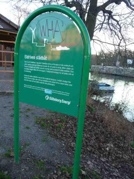 Eldriven städbåt skymtar i Vallgraven vid Trädgårdsföreningen och Slussbron. Söndag 24 november 2013 kl 14:55.