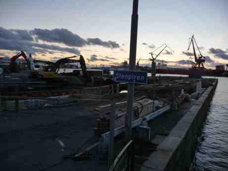 Kvällsarbete för grävskoporna på Stenpiren. Vid Götaverken på andra sidan Göta älv ligger M/S Primula. Torsdag 26 september 2013 kl 19:07.
