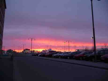 Solen går ner över Stenaterminalen vid Masthuggskajen. Men i rosenrött! Och sakta – borta 2020. Tisdag 25 mars 2014 kl 18:40.