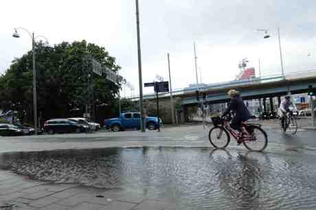 Cyklisterna riskerar att bli blöta om pedalfötterna efter skyfallet. Kanaltorgsgatan tisdag 19 augusti 2014 kl 17:44.