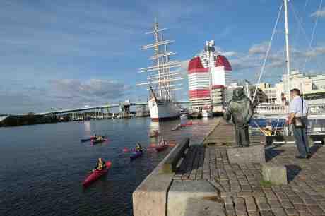 Kanotister från Lilla Bommens hamn passerar Evert Taube vid Jussi Björlings Plats framför operan. Måndag 1 september 2014 kl 18:20.