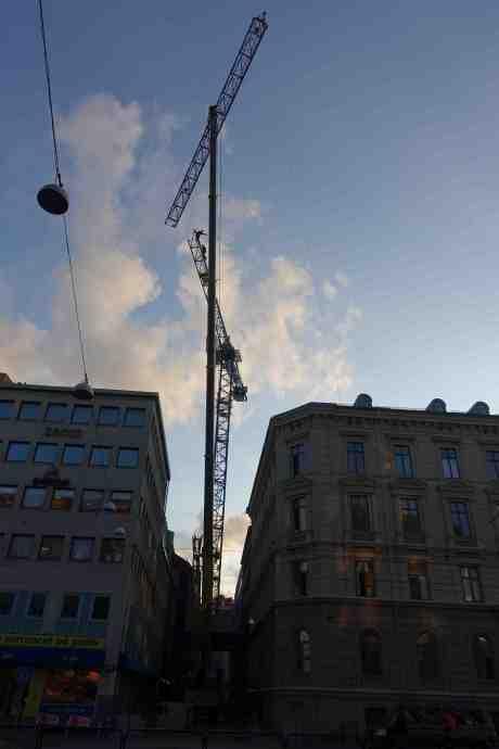 Svajmastartister (?) i en tornkran av modell Lindén som sätts upp på smala Klädpressaregatan i Västra Nordstaden. Torsdag 21 augusti 2014 kl 19:59.